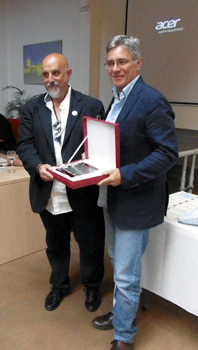 El alcalde, Juan Casanova, entrega un reconocimiento al diseñador de la cubierta del libro, Juanjo Trujillo.