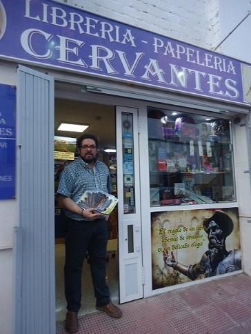 El librero de Librería Cervantes muestra ejemplares de Un paseo por Ronda.