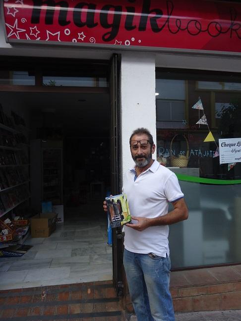 Rogelio Romero, en la entrada de Magik Books, con un ejemplar de Un paseo por Ronda.