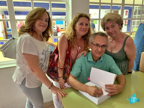 Rafael Ramos, durante la firma de ejemplares, con tres allegadas.